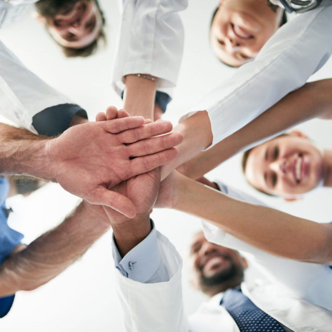 Shot of a diverse team of doctors joining their hands together in unity
